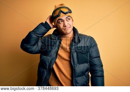 Young brazilian skier man wearing snow sportswear and ski goggles over yellow background confuse and wondering about question. Uncertain with doubt, thinking with hand on head. Pensive concept.