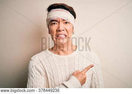 Young handsome chinese man injured for accident wearing bandage and strips on head Pointing aside worried and nervous with forefinger, concerned and surprised expression