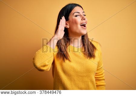 Young beautiful woman wearing casual sweater over yellow isolated background smiling with hand over ear listening an hearing to rumor or gossip. Deafness concept.