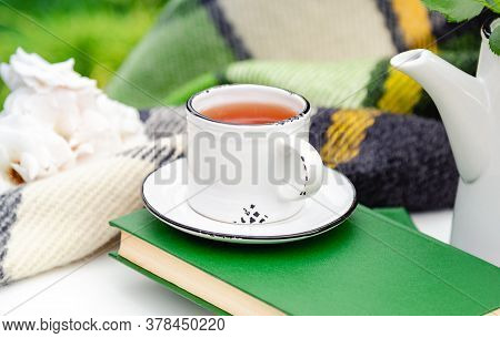 White Cup Of Tea On Books With Green Warm Plaid, Spring Flowers On White Table Outdoor. Hot Drink At