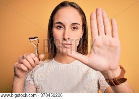 Young beautiful woman using eyelash curler standing over isolated yellow background with open hand doing stop sign with serious and confident expression, defense gesture