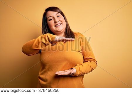 Beautiful brunette plus size woman wearing casual sweater over isolated yellow background gesturing with hands showing big and large size sign, measure symbol. Smiling looking at the camera. Measuring