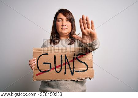 Plus size woman holding stop guns cardboard banner warning about violence with open hand doing stop sign with serious and confident expression, defense gesture