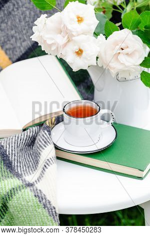 Vintage Cup Of Tea Near Open Book, Flowers White Wild Rose In Vase, Warm Plaid On White Table Outsid