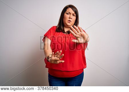 Beautiful brunette plus size woman wearing casual red t-shirt over isolated white background Moving away hands palms showing refusal and denial with afraid and disgusting expression. Stop.