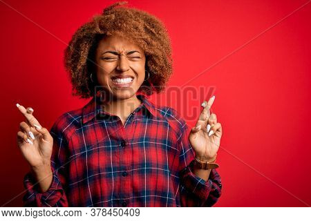 Young beautiful African American afro woman with curly hair wearing casual shirt gesturing finger crossed smiling with hope and eyes closed. Luck and superstitious concept.