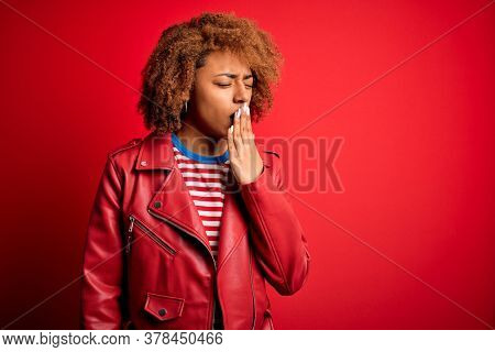 Young beautiful African American afro woman with curly hair wearing casual red jacket bored yawning tired covering mouth with hand. Restless and sleepiness.