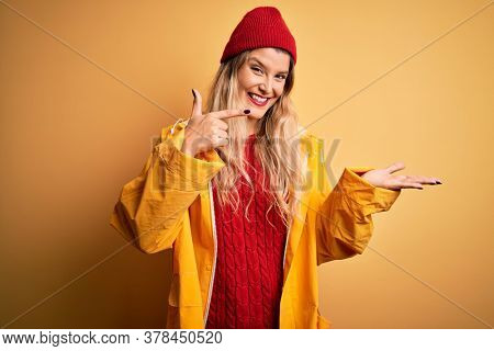 Young beautiful blonde woman wearing raincoat and wool cap over isolated yellow background amazed and smiling to the camera while presenting with hand and pointing with finger.