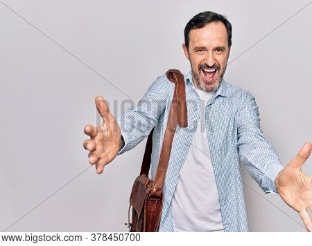 Middle age handsome businessman wearing leather bag over isolated white background looking at the camera smiling with open arms for hug. Cheerful expression embracing happiness.