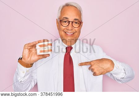 Middle age senior grey-haired dentist man holding prosthesis denture over pink background with surprise face pointing finger to himself