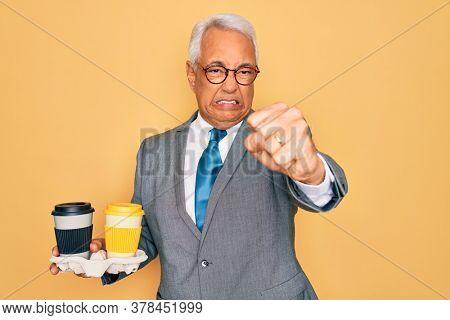 Middle age senior grey-haired business man wearing glasses holding coffee cup on tray annoyed and frustrated shouting with anger, crazy and yelling with raised hand, anger concept