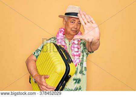 Middle age senior grey-haired man on holiday holding vacation suitcase over yellow background with open hand doing stop sign with serious and confident expression, defense gesture