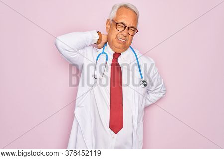 Middle age senior grey-haired doctor man wearing stethoscope and professional medical coat Suffering of neck ache injury, touching neck with hand, muscular pain