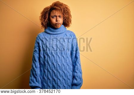 Young beautiful African American afro woman with curly hair wearing blue turtleneck sweater puffing cheeks with funny face. Mouth inflated with air, crazy expression.