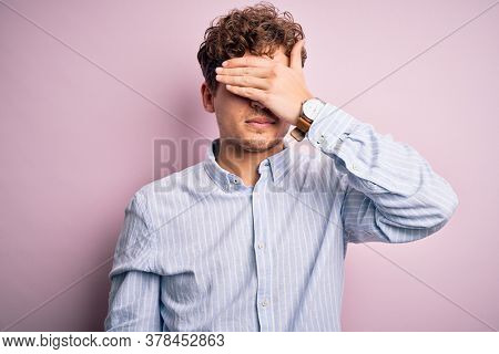 Young blond handsome man with curly hair wearing striped shirt over white background covering eyes with hand, looking serious and sad. Sightless, hiding and rejection concept