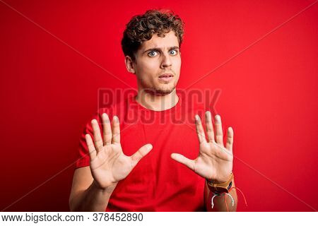 Young blond handsome man with curly hair wearing casual t-shirt over red background Moving away hands palms showing refusal and denial with afraid and disgusting expression. Stop and forbidden.