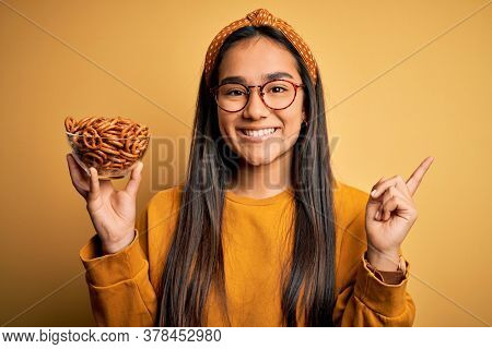 Young beautiful asian woman holding bowl with german baked pretzels over yellow background very happy pointing with hand and finger to the side