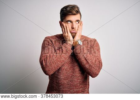 Young blond man with beard and blue eyes wearing casual sweater over white background Tired hands covering face, depression and sadness, upset and irritated for problem