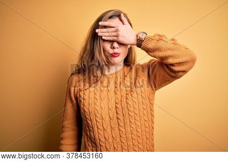 Young beautiful blonde woman wearing casual sweater standing over yellow background covering eyes with hand, looking serious and sad. Sightless, hiding and rejection concept