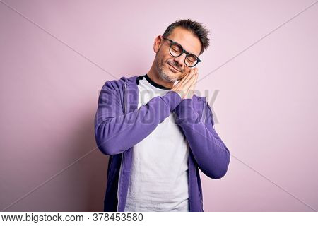 Young handsome man wearing purple sweatshirt and glasses standing over pink background sleeping tired dreaming and posing with hands together while smiling with closed eyes.