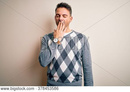 Young handsome man wearing casual sweater standing over isolated white background bored yawning tired covering mouth with hand. Restless and sleepiness.