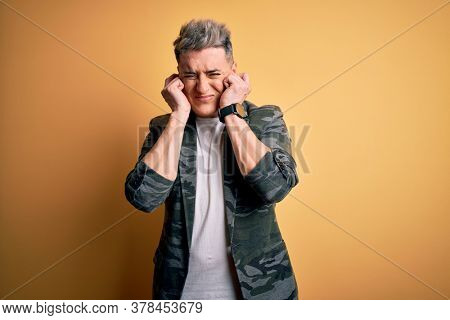 Young handsome modern man wearing business jacket standing over yellow isolated background covering ears with fingers with annoyed expression for the noise of loud music. Deaf concept.