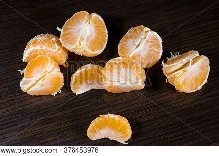 Lobules Of Mandarin On Dark Wooden Table