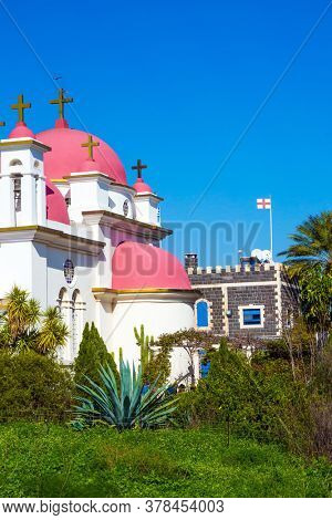 Israel. Snow-white church with pink domes and golden crosses. Gorgeous green south park. Orthodox monastery of the Twelve Apostles. The concept of religious pilgrimage and photo tourism