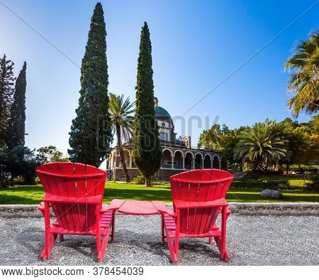 Catholic Church of the Beatitudes and park around the monastery. Two comfortable red chairs - deck chairs on the platform for relaxing. The concept of religious pilgrimage and photo tourism