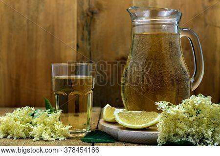 A Glass And Pitcher Of Homemade Natural Elderflower Juice With Lemon And Elder Blossoms On Old Woode