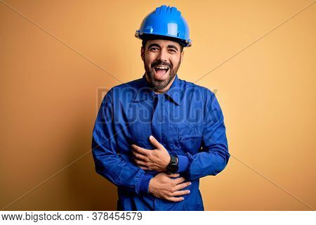 Mechanic man with beard wearing blue uniform and safety helmet over yellow background smiling and laughing hard out loud because funny crazy joke with hands on body.