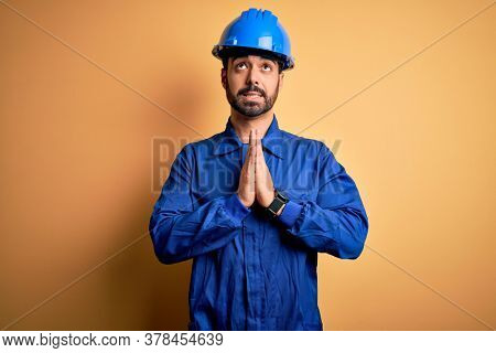 Mechanic man with beard wearing blue uniform and safety helmet over yellow background begging and praying with hands together with hope expression on face very emotional and worried. Begging.