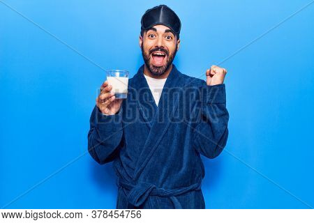 Young hispanic man wearing sleep mask and robe drinking milk screaming proud, celebrating victory and success very excited with raised arm