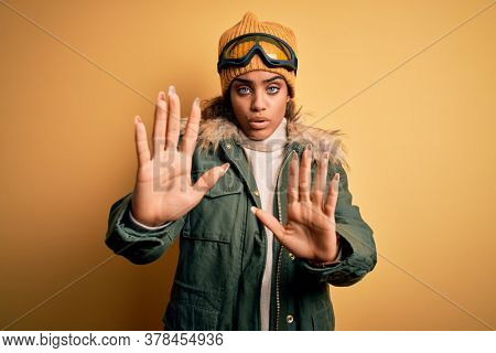 Young african american afro skier girl wearing snow sportswear and ski goggles Moving away hands palms showing refusal and denial with afraid and disgusting expression. Stop and forbidden.