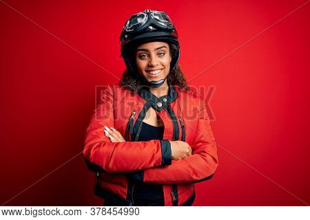 Young african american motorcyclist girl wearing moto helmet and glasses over red background happy face smiling with crossed arms looking at the camera. Positive person.