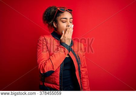 Beautiful african american girl wearing red jacket and sunglasses over isolated background bored yawning tired covering mouth with hand. Restless and sleepiness.