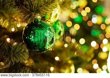 Decorated Christmas Tree Closeup. Green And Golden Christmas Ornament Balls And Garland With Golden