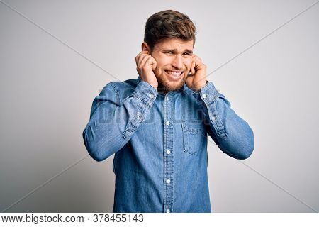 Young handsome blond man with beard and blue eyes wearing casual denim shirt covering ears with fingers with annoyed expression for the noise of loud music. Deaf concept.