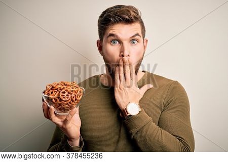 Young blond German man with beard and blue eyes holding bowl with baked pretzel cover mouth with hand shocked with shame for mistake, expression of fear, scared in silence, secret concept