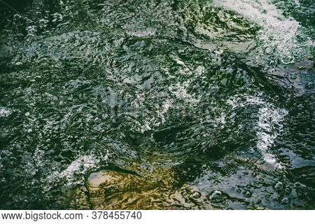 Green Water Surface With Bubbles Close-up. Background Of Green Soda Drink Water. Nature Texture Of S