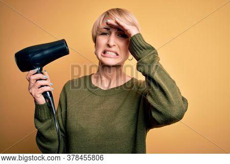 Young blonde woman with short hair drying her hair using hairdryer over yellow background stressed with hand on head, shocked with shame and surprise face, angry and frustrated. Fear and upset.