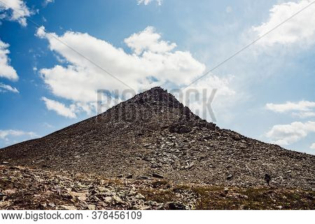 Atmospheric Mountain Landscape With Gray Rock Pinnacle Under Blue Cloudy Sky. Awesome Highland Scene
