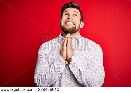 Young blond businessman with beard and blue eyes wearing elegant shirt over red background begging and praying with hands together with hope expression on face very emotional and worried. Begging.