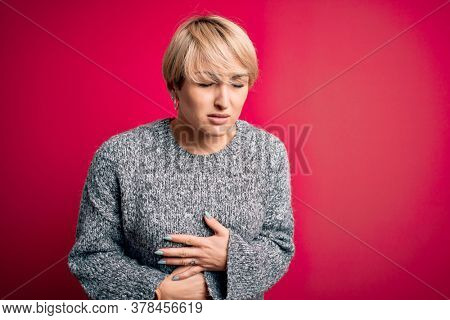 Young blonde woman with modern short hair wearing casual sweater over pink background with hand on stomach because indigestion, painful illness feeling unwell. Ache concept.