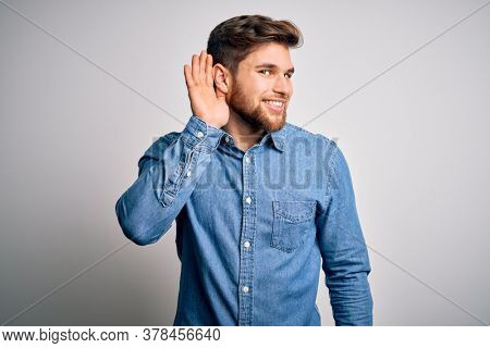 Young handsome blond man with beard and blue eyes wearing casual denim shirt smiling with hand over ear listening an hearing to rumor or gossip. Deafness concept.