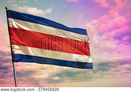 Fluttering Costa Rica Flag On Colorful Cloudy Sky Background. Costa Rica Prospering Concept.