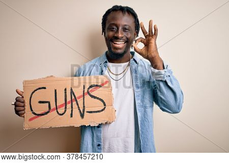 Young african american man asking for peace holding banner with prohibited guns message doing ok sign with fingers, excellent symbol