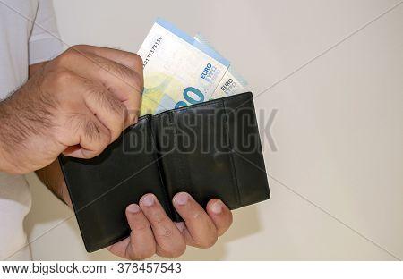 European Union Currency. Euro Money Banknotes. Man In White T Shirt Put Euro Banknotes Into Black Wa