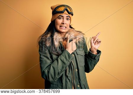 Young beautiful hispanic woman wearing ski glasses and coat for winter weather Pointing aside worried and nervous with both hands, concerned and surprised expression