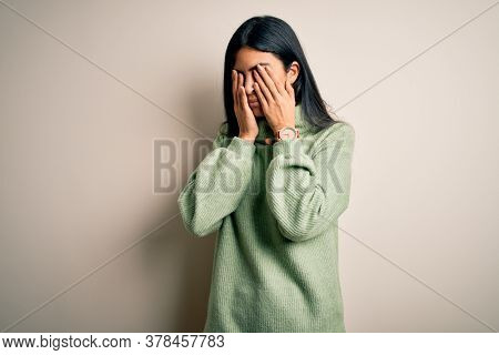 Young beautiful hispanic woman wearing green winter sweater over isolated background rubbing eyes for fatigue and headache, sleepy and tired expression. Vision problem